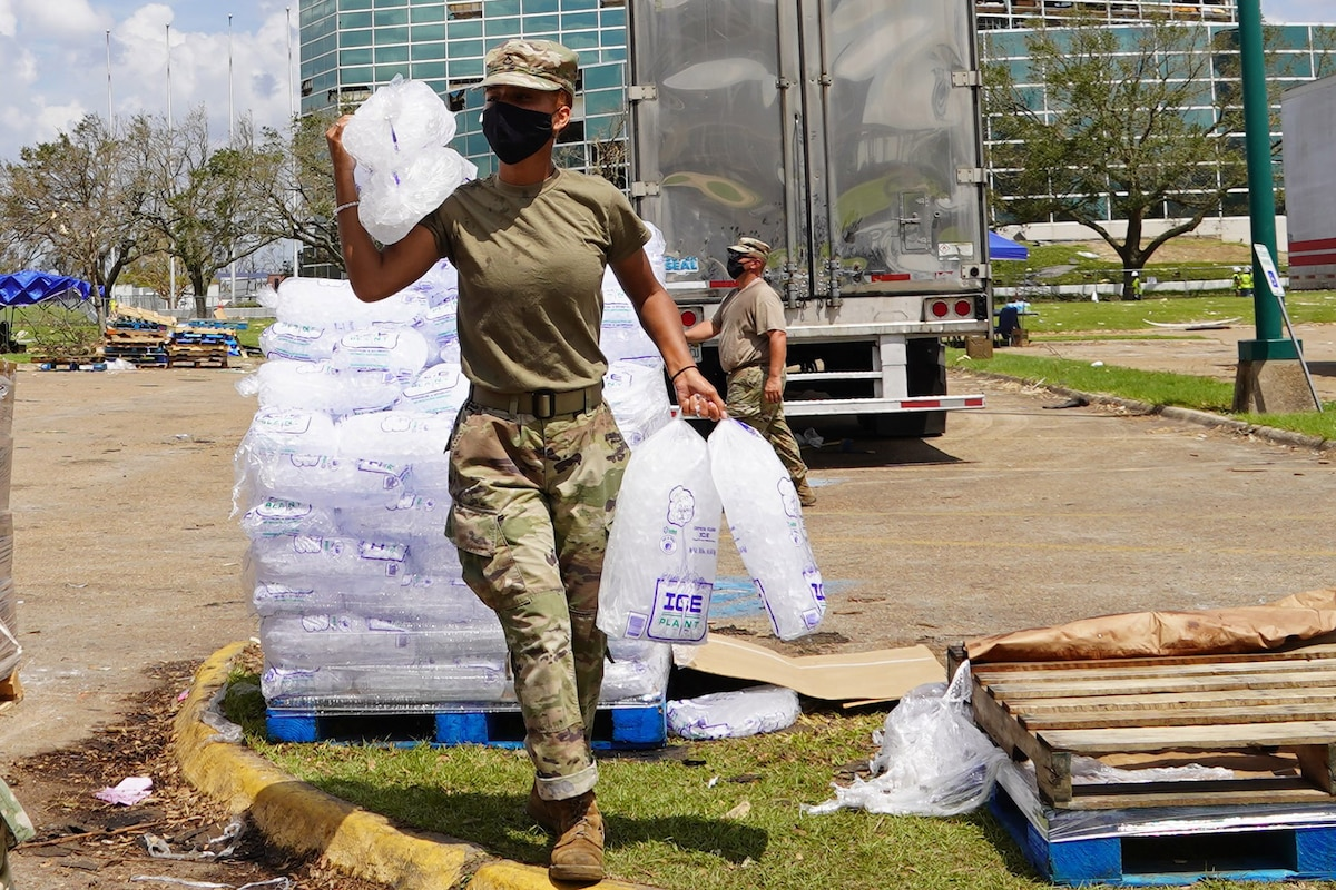 A soldier carries bags of ice.
