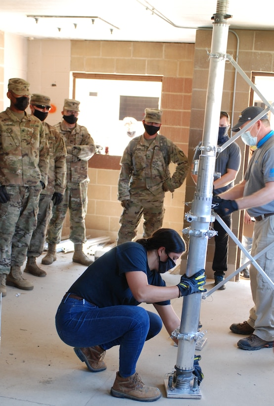 Dr. Genenvieve Pezzola, a U.S. Army Engineer Research and Development Center (ERDC) research civil engineer and team leader for the Expedient Retrofit for Existing Buildings (EREB) system, carefully shows Soldiers from the 5th Engineer Battalion how to properly secure each piece of the EREB system. During the Maneuver Support, Sustainment and Protection Integration Experiments-2020, or MSSPIX-20, demonstrations, researchers from the ERDC tested three different protection technologies and demonstrated the capability of each system, collected data and validated the performance and new system upgrades at Training Area 230 on Fort Leonard Wood, Mo., Aug. 17, 2020.