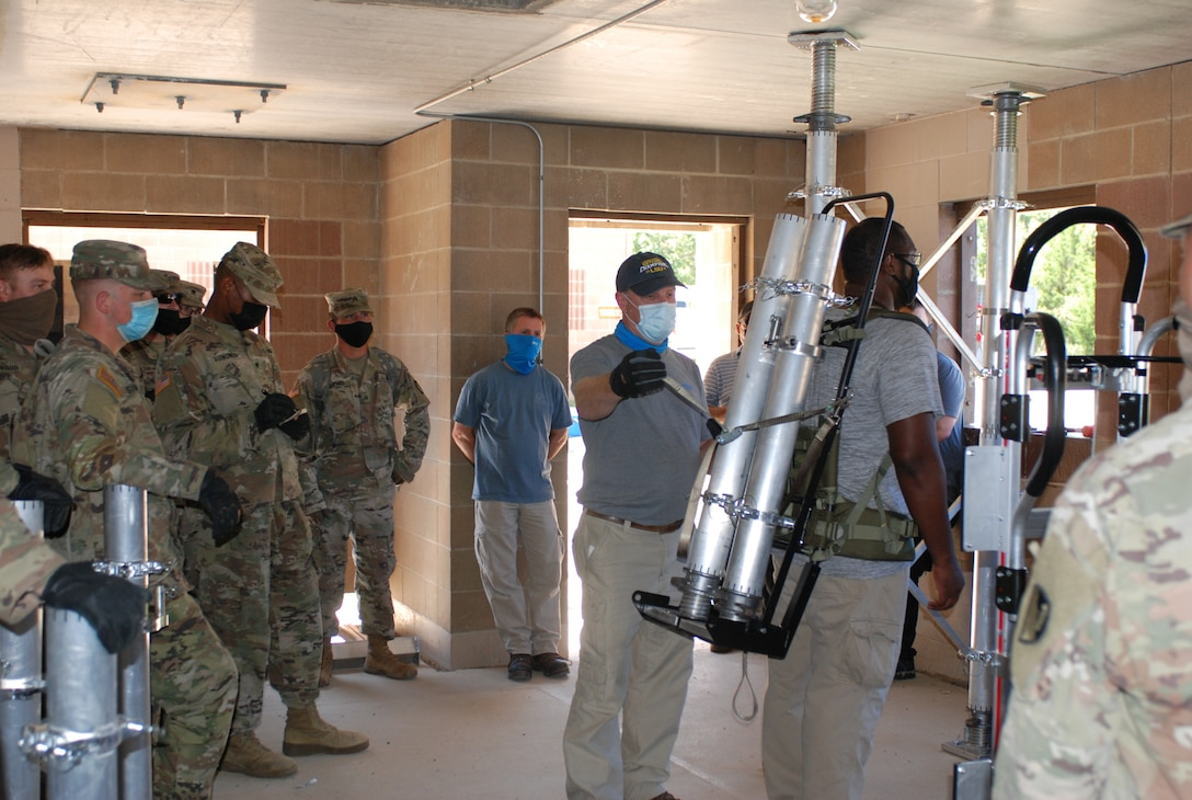 U.S. Army Engineer Research and Development Center instructors demonstrate the proper technique to safely secure and carry the pieces of the Expedient Retrofit for Existing Buildings system and quickly set it up inside an abandonded building at Training Area 230 on Fort Leonard Wood, Mo., during the Maneuver Support, Sustainment and Protection Integration Experiments-2020, or MSSPIX-20, Aug. 17, 2020.