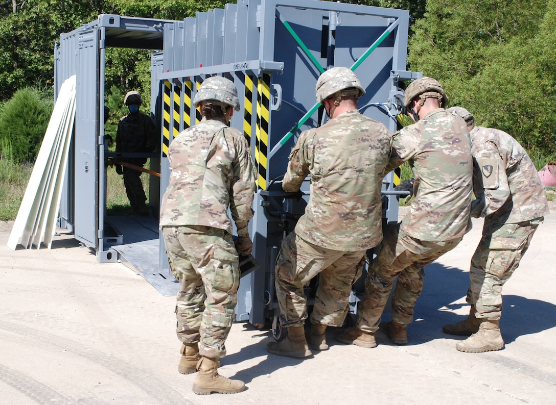 Soldiers from 5th Engineer Battalion extract the Ready Armor Protection for Instant Deployment, or RAPID, system from its storage container to secure the entrance way of Training Area 230 on Fort Leonard Wood, Mo., during the Maneuver Support, Sustainment and Protection Integration Experiments-2020 Aug. 17, 2020. Researchers from the U.S. Army Engineer Research and Development Center provided this protection technology to test and demonstrate the capability of the system and validate its performance.