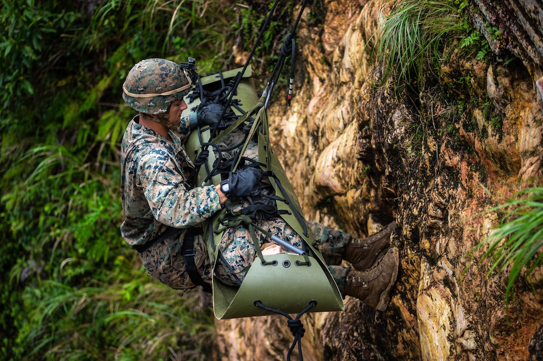 U.S. Marines participate in a simulated casualty evacuation via rappelling drills of the Infantry Jungle Skills Course at the Jungle Warfare Training Center on Camp Gonsalves, Okinawa, Japan, Sept. 10.