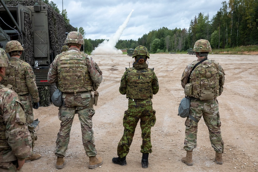Soldiers assigned to Bravo Battery, 1st Battalion, 6th Field Artillery Regiment and soldiers from the Estonian Defence Force watch as a rocket takes flight in the distance during live fire exercise with Estonian Defense Force in Tapa, Estonia Sept. 5, 2020.