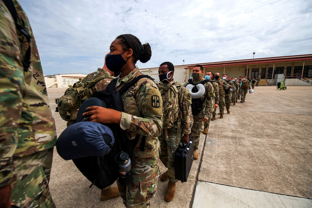 Soldiers wearing face masks line up to board a plane.