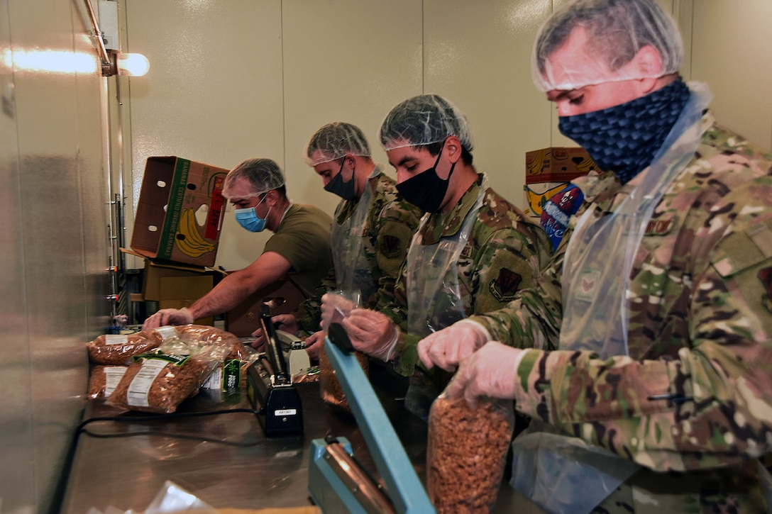 Air National Guardsmen wearing face masks handle food.