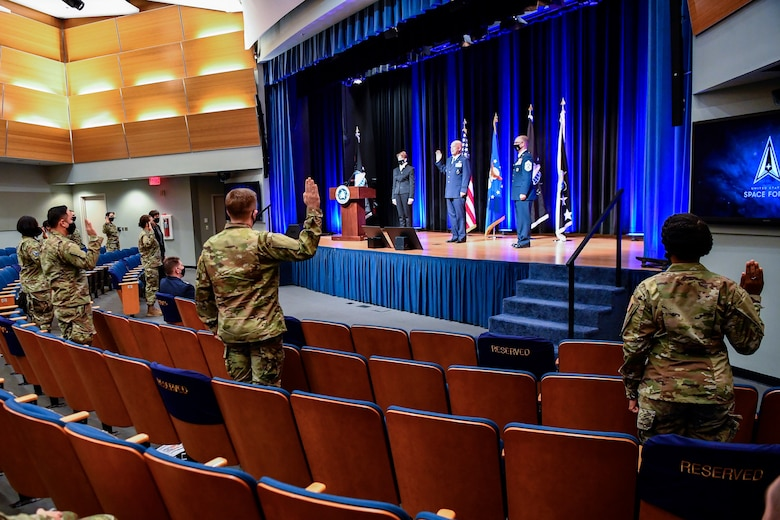 Chief of Space Operations Gen. John W. Raymond, center rear, administers the oath of office to airmen transferring into the U.S. Space Force during a ceremony at the Pentagon, Arlington, Va., Sept. 15, 2020. About 300 airmen at bases worldwide, including 22 in the audience, transferred during the ceremony.  (U.S. Air Force photo by Eric R. Dietrich)