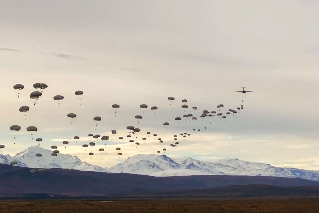 A large group of soldiers free fall wearing parachutes with snowy mountains in the background.