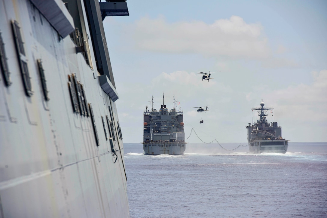 Two ships sail next to each other as two helicopters fly above.