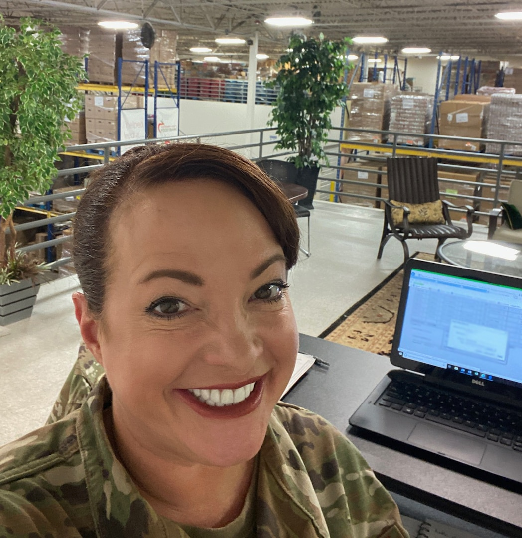 Female wearing her Air Force uniform is working in a warehouse with a lot of pallets