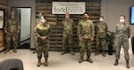 Military personnel wearing masks stand in front of a Montgomery County Food Bank sign