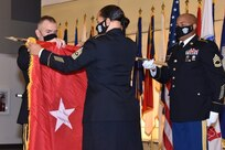 Army Medical Logistics Command Commander Brig. Gen. Michael Lalor, left, unfurls the new one-star flag with Sgt. Maj. Monnet Bushner, middle, during a promotion ceremony at Fort Detrick, Maryland, on Sept. 11. Sgt. 1st Class Brian Ockimey holds the flag staff. (Photo Credit: Ellen Crown)