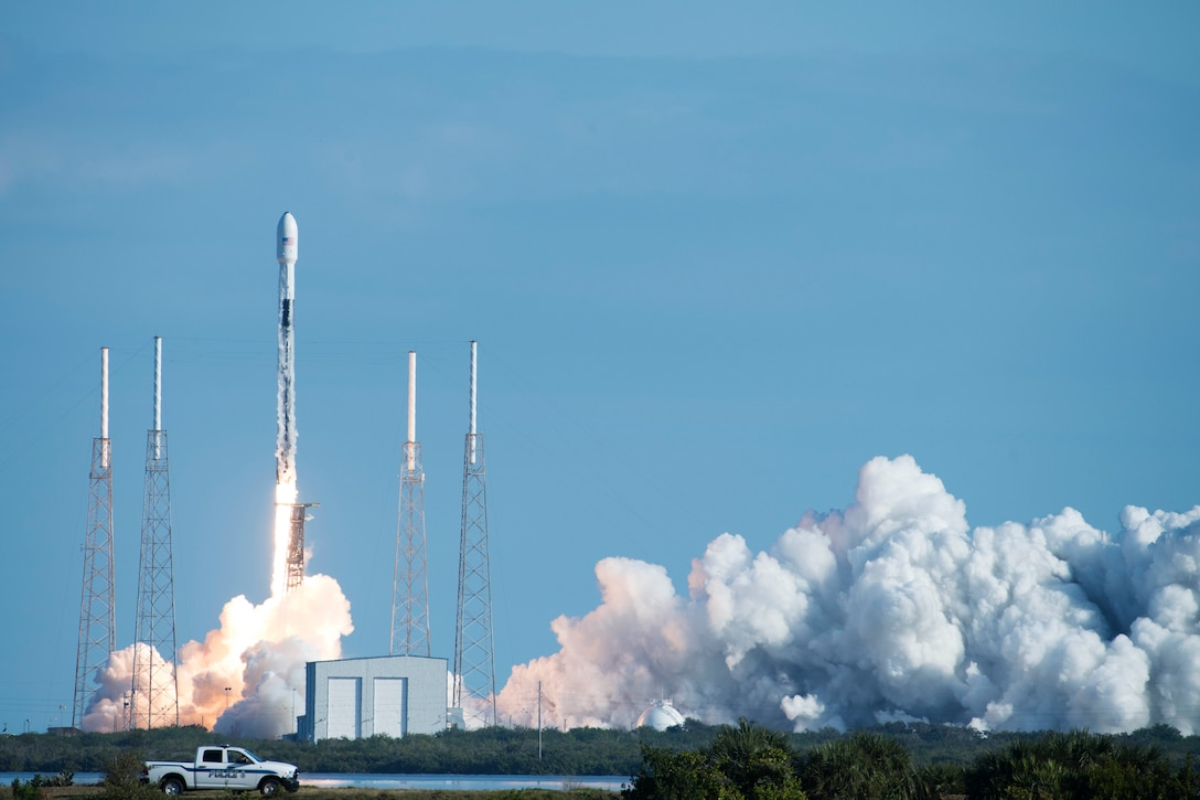 A rocket launches against a blue sky.  Flames and smoke billow out underneath.