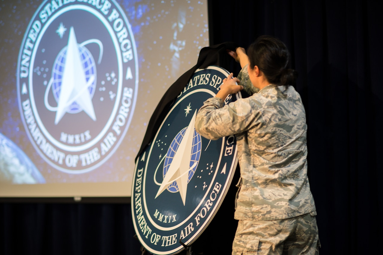 An airman pulls a black sheet off an easel that holds a circular cutout featuring the seal of the U.S. Space Force.