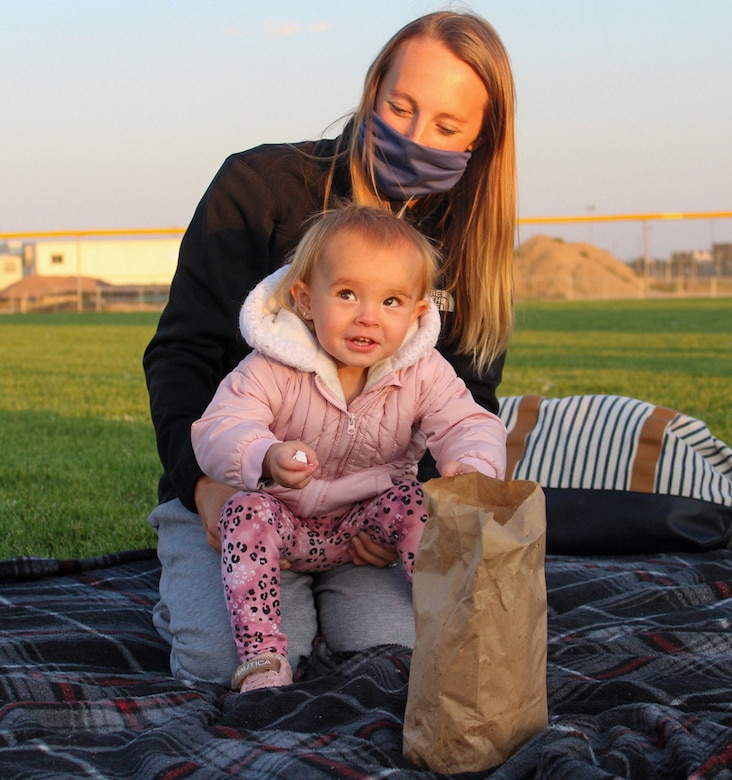 "Olivia, 2, reaches for popcorn while her mom, Kaley Raike, holds her Sept. 11, 2020, at Schriever Air Force Base, Colorado. The 50th Force Support Squadron's Movie Night in the Park hosted more than 60 people to watch ""Aladdin."" (U.S. Air Force photo by Marcus Hill)"
