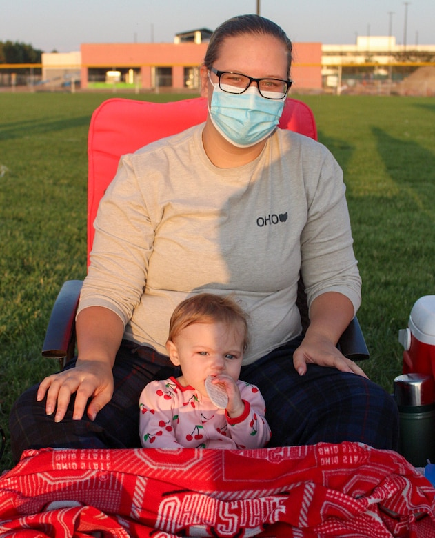 "Reid, nine months, nibbles on a teething snack while her mother, Schenly Wheeler, 50th Force Support Squadron, awaits the start of the movie ""Aladdin"" at the softball field at Schriever Air Force Base, Colorado, during the 50th Force Support Squadron's Movie Night at the Park Sept. 11, 2020. The 50th FSS is scheduled to host another movie night 7 p.m. Sept. 28 featuring ""The Lion King,"" which will include a comedy show and magician from 6-7 p.m. (U.S. Air Force photo by Marcus Hill)"