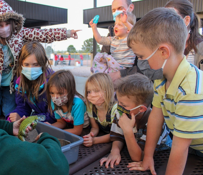 "Children gather to see ""Wakanda,"" a Moroccan, spiny-tailed lizard, Sept. 11, 2020, at Schriever Air Force Base, Colorado. Prior to the 50th Force Support Squadron showing ""Aladdin"" for Movie Night in the Park, the Cheyenne Mountain Zoo provided entertainment, including a pair of lizards and animal furs and skulls for viewing. (U.S. Air Force photo by Marcus Hill)"