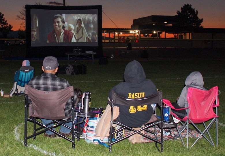 "Families watch the movie ""Aladdin"" during the 50th Force Support Squadron's Movie Night in the Park Sept. 11, 2020, at Schriever Air Force Base, Colorado. The 50th FSS sprayed circles on the field to keep eventgoers six feet apart to adhere to physical distancing guidelines. (U.S. Air Force photo by Marcus Hill)"