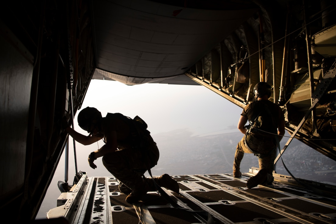 Loadmasters look out a plane