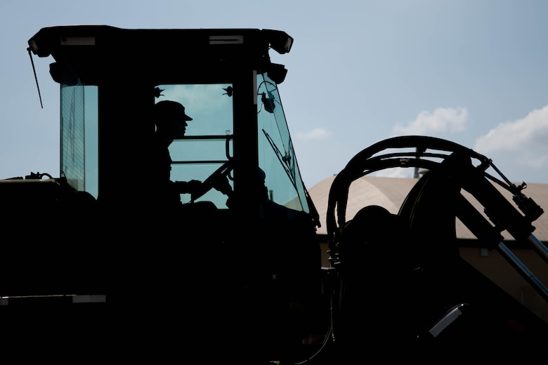 silhouette of man driving heavy machinery