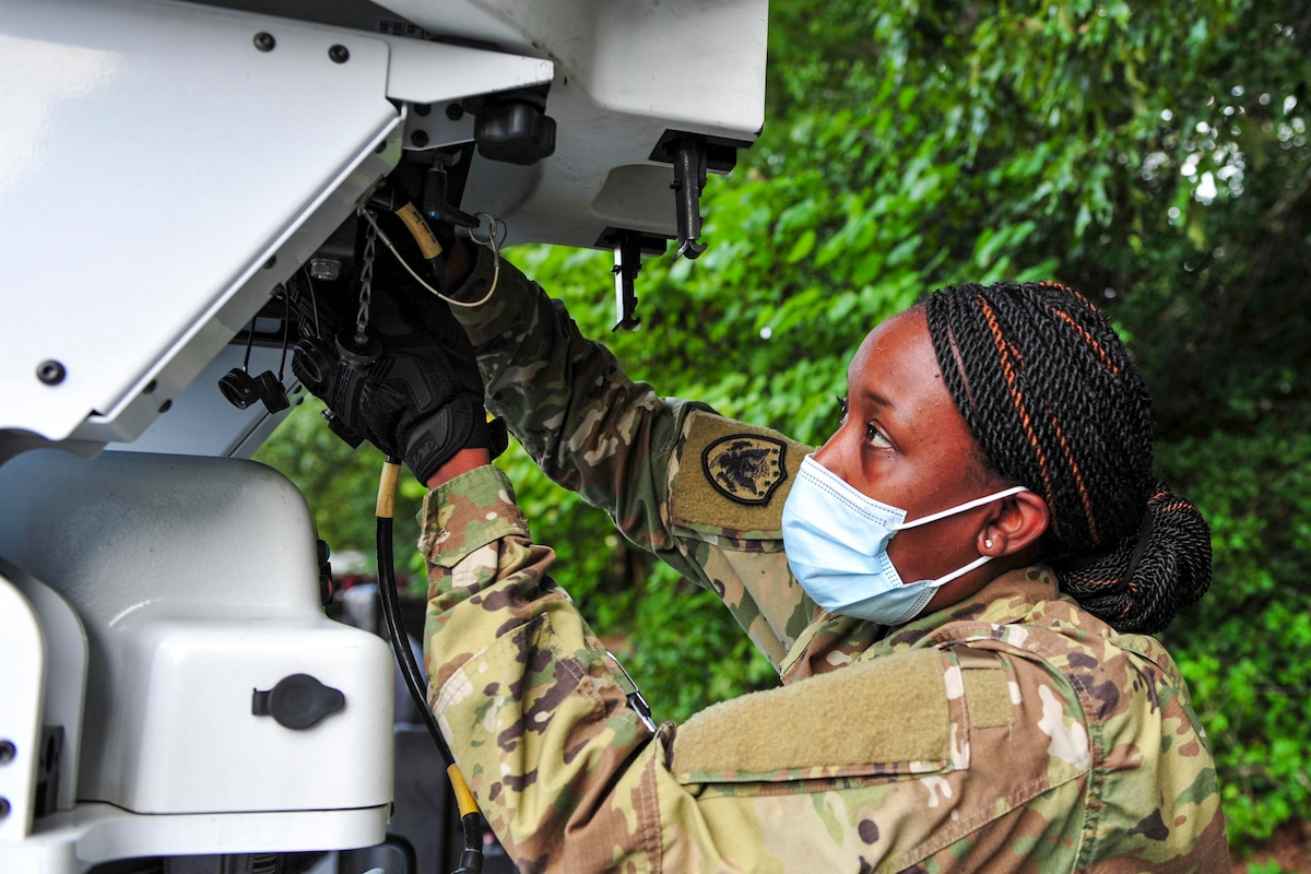 An airman wearing a face mask attaches a power supply to a satellite.