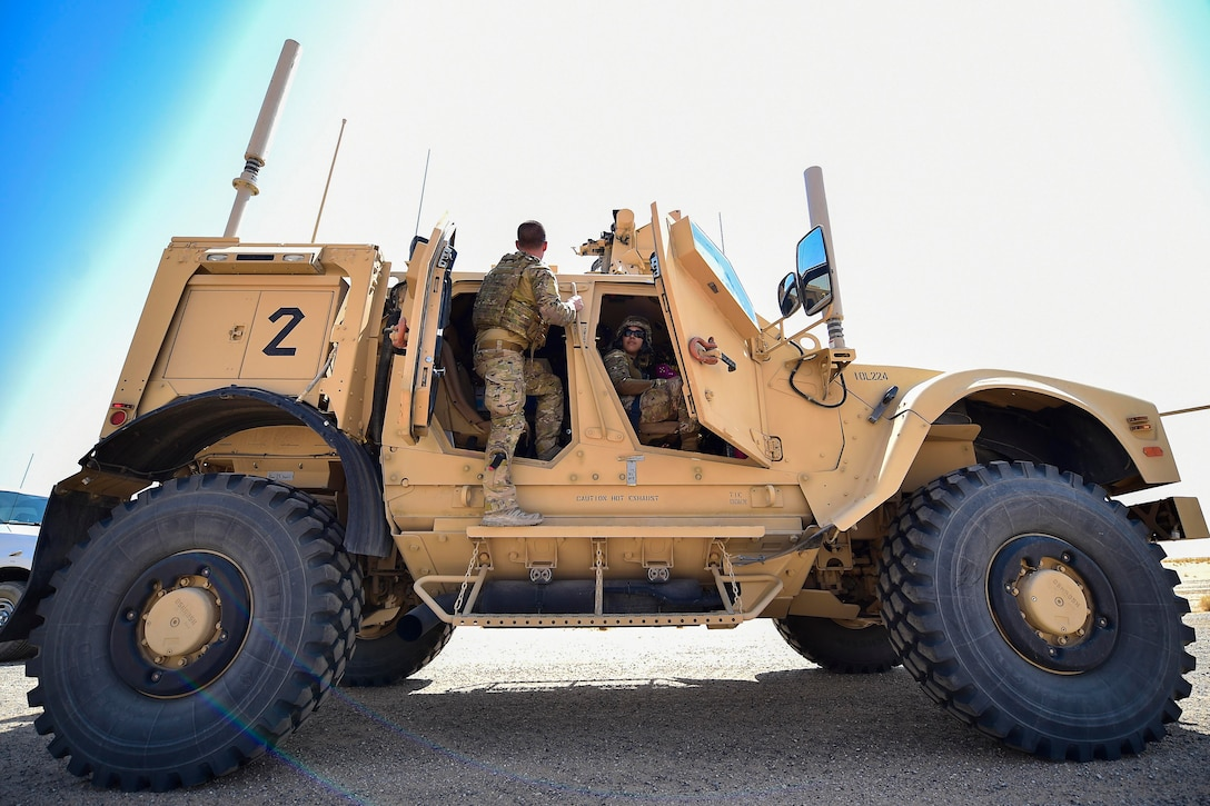 Airmen stand and sit inside a military vehicle.