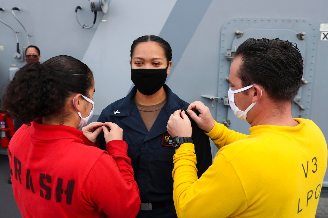 Two sailors place pins on another sailor's uniform.