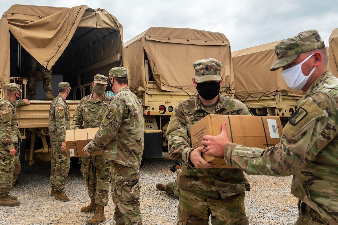 A group of soldiers unload boxes from a vehicle.
