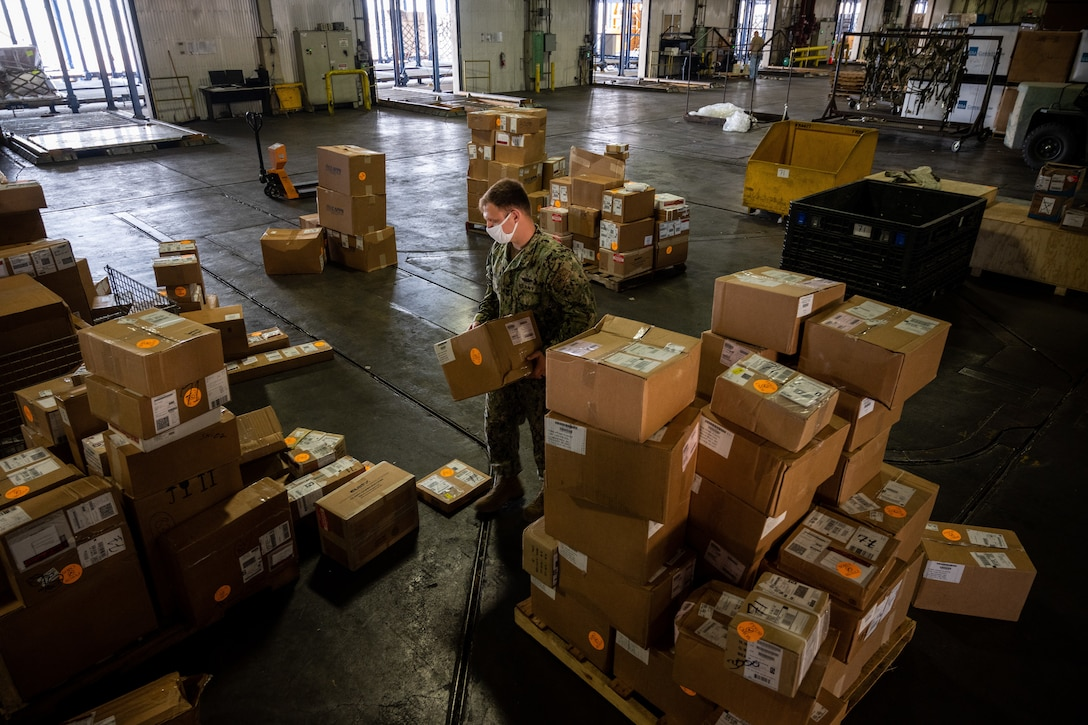 A Navy service member stacks boxes inside a large warehouse.