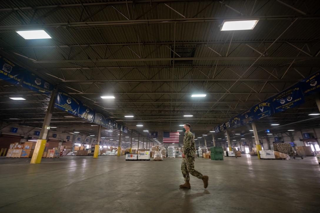A Navy service member walks across a large warehouse floor.