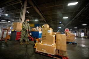 A Navy service member moves a small pallet of boxes inside a large warehouse.