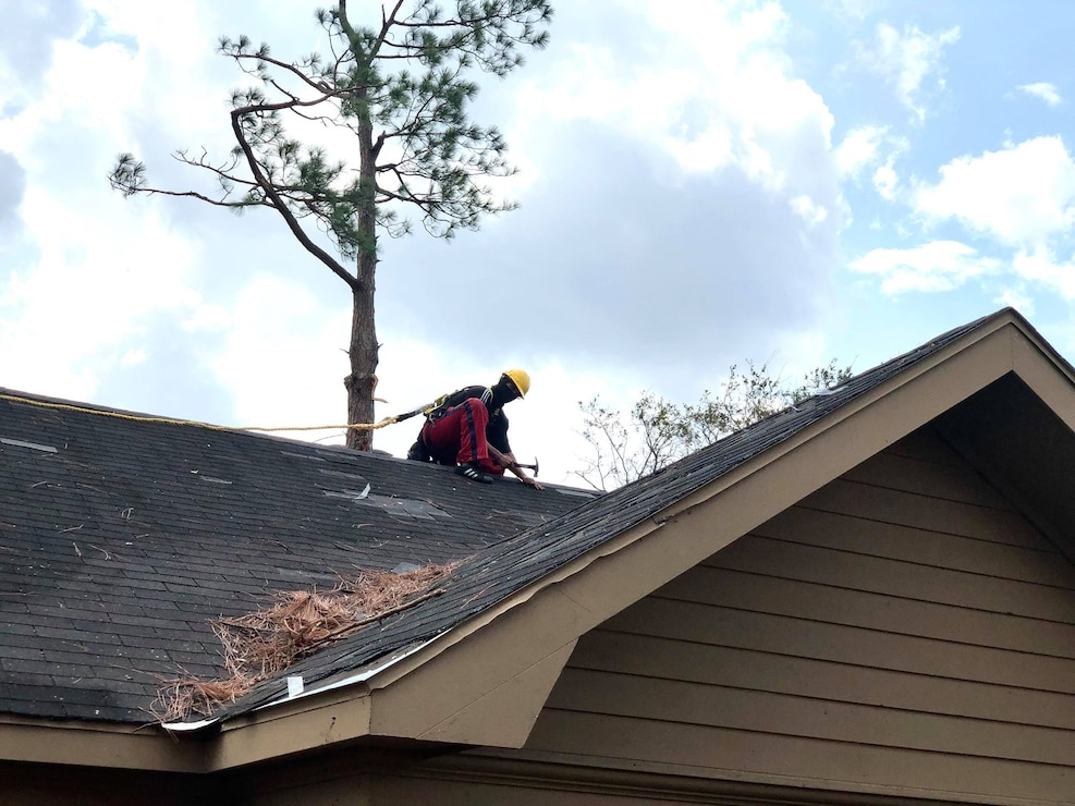 IN THE PHOTO, a U.S. Army Corps of Engineers contractors works on installing a temporary 'blue roof' for a homeowner who applied for the free assistance program. The purpose of the Blue Roof Program is to provide homeowners in disaster areas with fiber-reinforced sheeting to cover damaged roofs until permanent repairs can be made. The deadline to sign up for this free assistance is Sept. 30, 2020. (USACE photo by Lt. Col. Nathan Molica)