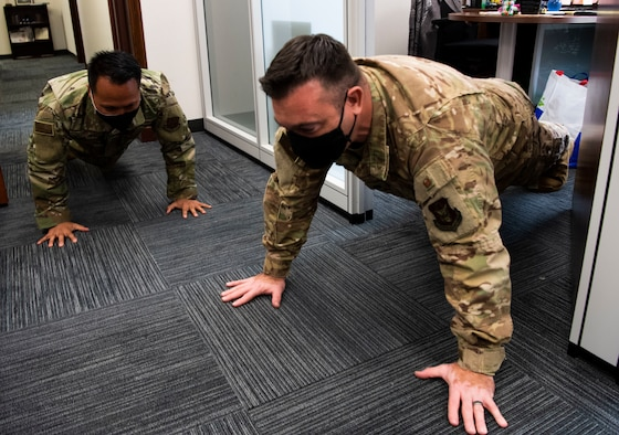 A photo of U.S. Air Force Staff Sgt. Mark Corpuz and Lt. Col. Cliff Harris, both who are part of the 624th Regional Support Group command staff, doing push-ups as part of a Resiliency Tactical Pause at Joint Base Pearl Harbor-Hickam, Hawaii, Sept. 12, 2020, during the Group's Unit Training Assembly.