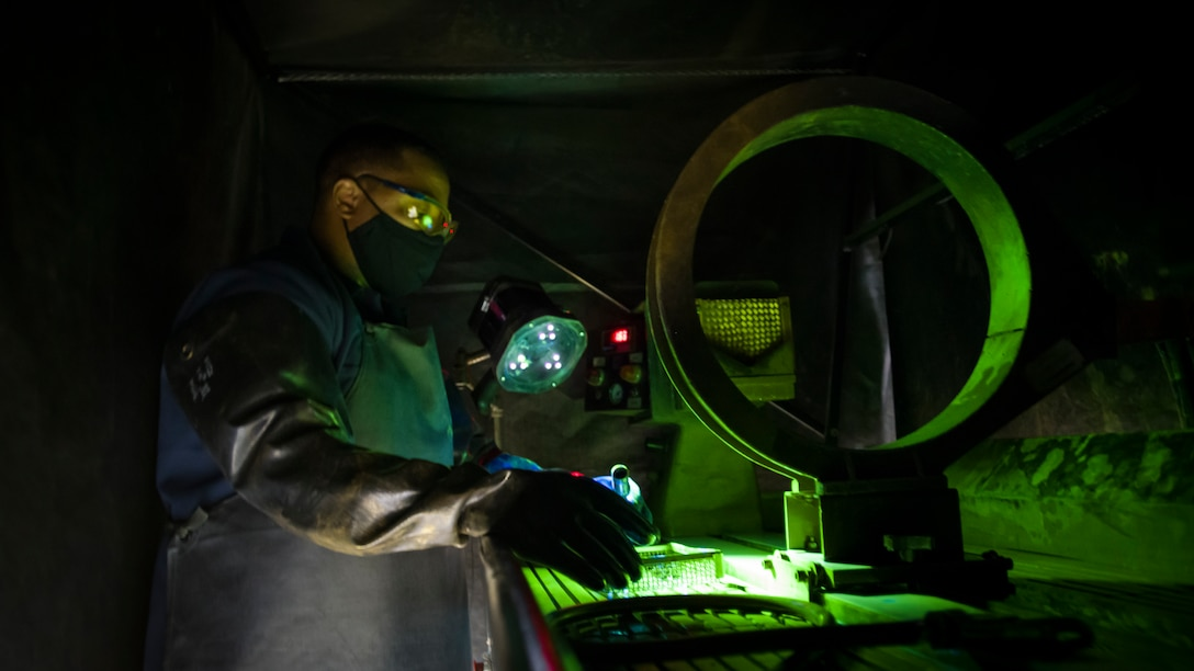 Tech. Sgt. Corey Nichols, a non-destructive inspection technician with the 177th Fighter Wing, Atlantic City International Airport, New Jersey, inspects aircraft parts utilizing a UV light at Edwards Air Force Base, California, July 24. (Air Force photo by Giancarlo Casem)