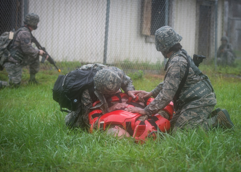 An airman takes down a simulated adversary while another airman helps.