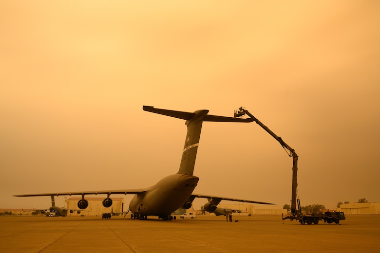 Airmen are lifted in a large condor lift above a C-5M tail with a smokey, yellowish sky.