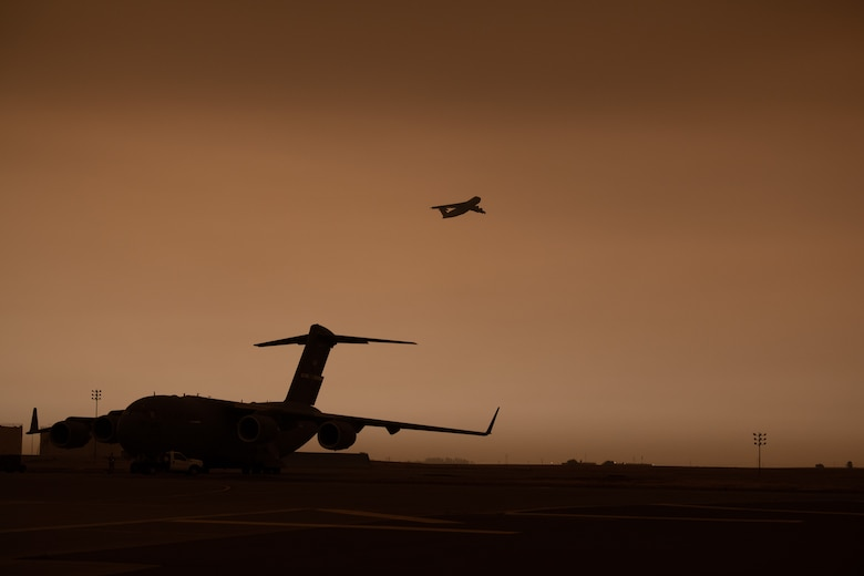 A C-5M takes off on the flight line with a yellowish, smokey sky.