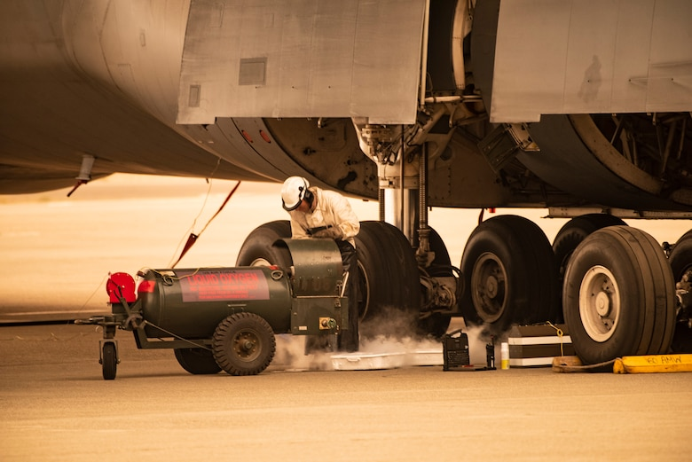 U.S. Air Force Airman 1st Class Ricardo Puente, 60th Aircraft Maintenance Squadron crew chief, services the oxygen system of a C-5M Super Galaxy Sept. 9, 2020 at Travis Air Force Base, California. Wildfires across California propelled smoke and ash into the troposphere, impacting air quality. (U.S. Air Force photo by Heide Couch)