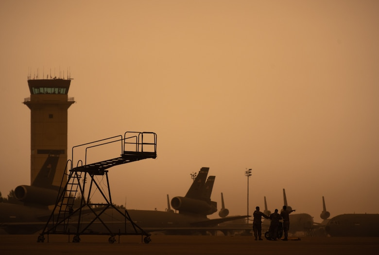 Airmen on the flight line with a smokey, yellowish sky.