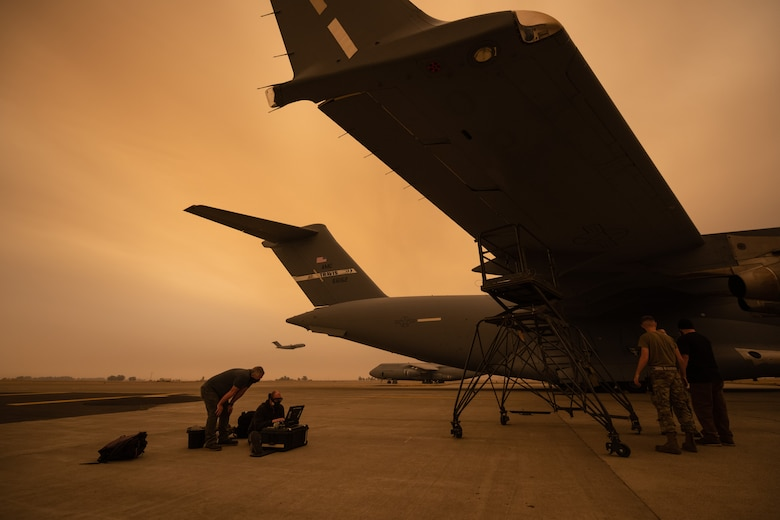 Airmen work on a wing of a C-17 while another C-17 takes off in the background.