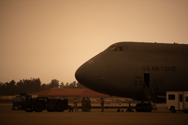 Airmen attach a towing vehicle to a C-5M on the flight line with a yellowish, smokey sky.