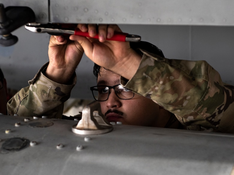 A U.S. Air Force Airman, assigned to the 48th Component Maintenance Squadron fuels systems maintenance shop, works to attach an external fuel tank to an F-15C Eagle during an Agile Combat Employment training at Royal Air Force Lakenheath, England, Aug. 31, 2020. The training was designed to enhance ACE  capabilities by teaching Airmen to perform multiple roles outside the scope of their regular daily duties. (U.S. Air Force photo by Airman 1st Class Jessi Monte)