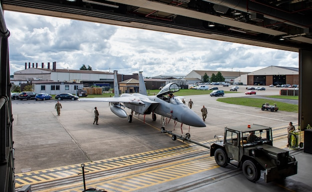 U.S. Air Force Airmen, assigned to the 48th Component Maintenance Squadron fuels systems maintenance shop, tow an F-15C Eagle into the hangar during an Agile Combat Employment training at Royal Air Force Lakenheath, England, Aug. 31, 2020. Proficiency in a multitude of skills allows Airmen to more effectively and efficiently respond to unique scenarios and potential threats, which is a key aspect of the ACE initiative. (U.S. Air Force photo by Airman 1st Class Jessi Monte)