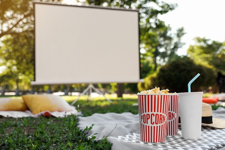 photo shows movie screen outdoors with popcorn and soda in the forefront.