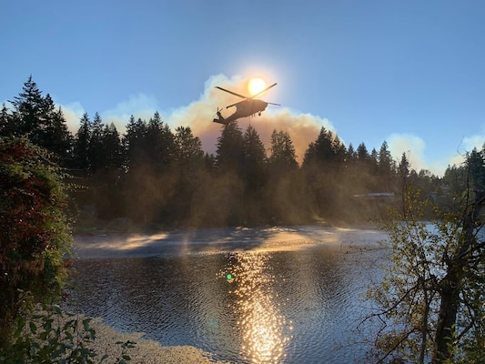 A Washington Army National Guard Black Hawk helicopter loads up a water bucket in a lake near Bonney Lake, Wash., Sept 9, 2020. Washington National Guard flight crews dropped more than 280,000 gallons of water on the Sumner Grade Fire.
