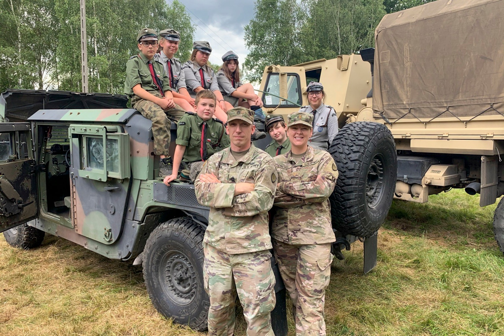 U.S. Army Sgt. 1st Class Dayton Will, left, Forward Operating Site Świętoszów deputy mayor and 2nd Lt. Balinda Dresel, FOS Świętoszów mayor, both with the Alaska National Guard's 297th Regional Support Group, with Polish scouts at Camp Watra near Osieczow, Poland, July 17, 2020. The Alaska Guardsmen and Reservist with the 266th Ordinance Company, out of Puerto Rico, and Bravo Company, 418th Civil Affairs Battalion, out of Missouri, learned about the history and values of the Polish scouting organization while sharing their units' missions and high-mobility multipurpose wheeled and medium tactical vehicles that are assigned to nearby FOS Świętoszów.