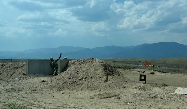 An airman throws a live grenade at a grenade range as part of a joint training exercise hosted by 1st Space Brigade, U.S. Army Space and Missile Defense Command, at Fort Carson, Colorado, Aug. 27. (U.S. Army photo by Dottie K. White)