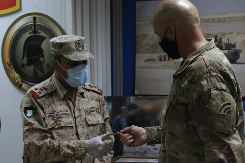 Kuwait military Brig. Gen. Khaled Al-Shualah is presented with a division coin from Brig. Gen. Thomas Spencer the 42nd Infantry Division Deputy Commander for Support on September 10, 2020 in Kuwait. The Two country have been working together to strengthen their partnership. (U.S. Army Photo by Sgt. Andrew Winchell)