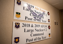 Signs commemorating the 2nd Bomb Wing command post's achievements hang at the entrance of the 2nd BW command post at Barksdale Air Force Base, La., Sept. 3, 2020. Barksdale's command post was awarded the 2018 and 2019 Air Force Global Strike Command Large Nuclear C2 Command Post of the Year as well as the 2019 Air Force Large NC2 Command Post of the Year. (U.S. Air Force photo by Airman 1st Class Jacob B. Wrightsman)