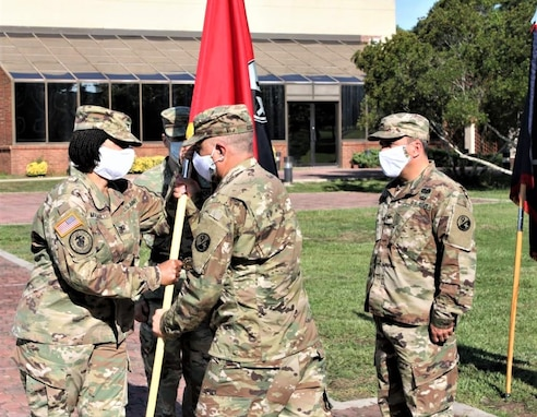 Command Sgt. Maj. Ronald Coots (right), 4th Brigade (Personnel Services) command sergeant major, passes the unit guidon to Col. Janene Marshall-Gatling (left), outgoing 4th Brigade (PS) commander, during the unit's change of command ceremony held on Victory Field at Fort Jackson, S.C., July 11, 2020. Marshall-Gatling served as the 4th Brigade (PS) commander for two years prior to her relinquishment of command to Col. Aaron Wilkes. (U.S. Army Reserve photo courtesy of 1st Lt. Matthew Rutledge, 4th Brigade (PS), 94th TD-FS)