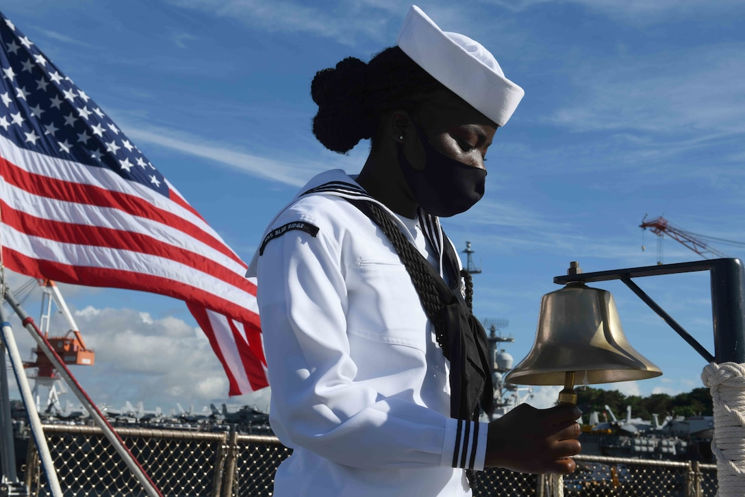 A sailor rings a bell on board a military ship.