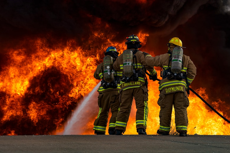 Airman Andrew Burr, 7th Civil Engineer Squadron firefighter, left, Senior Airman Thomas Drouillard, 445th CES firefighter, and Justin Raymundo, 7th CES firefighter extinguish a fire on an aircraft fire trainer at Dyess Air Force Base, Texas, Sept. 15, 2020. The firefighters tested a new ultra-high pressure fire hose that sprays a mist intended to cool the gasses surrounding the flames; earlier models typically blanket the flames with larger water droplets. (U.S. Air Force photo by Airman 1st Class Colin Hollowell)
